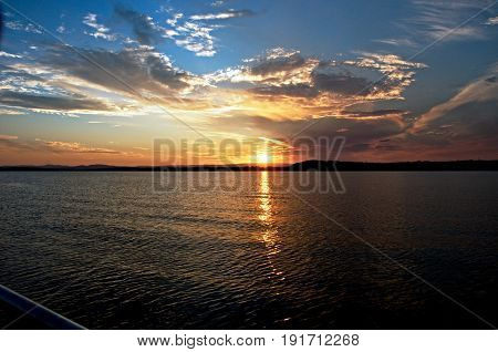 Vivid gold clouds and blue sky sunset seascape cloudscape with water reflections in the tranquil waters of Lake Macquarie at dusk.