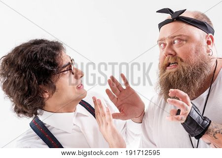 Now you will feel the real pain. Mad thick male hipster is pestering the young frightened student with eyeglasses. He is raising hands to beat the boy. Isolated