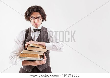 It is too much for me. Dissatisfied young smart man is holding heap of books. His lips protruded in a sulky pout. Isolated and copy space