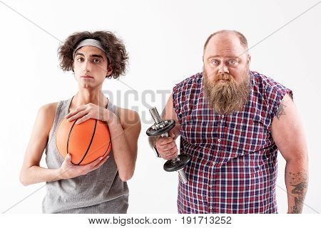 Portrait of strong fat man holding dumbbell and looking at camera with confidence. Slim guy is standing near him with basketball ball. Isolated