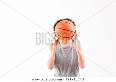 Scared slim boy is hiding his face behind basketball ball. He is standing. Isolated and copy space in left side