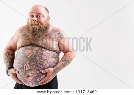Shy thick guy with beard is touching his tattooed big bare abdomen. He is standing and looking at camera with joy. Isolated and copy space