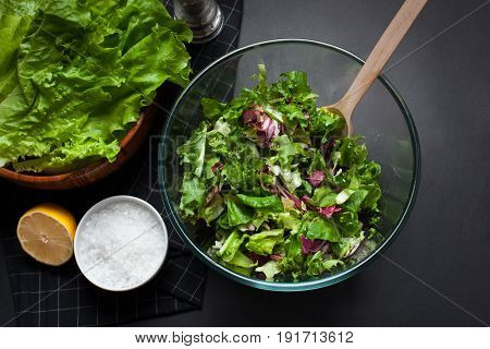Fresh vegetarian salad mix in a clear glass bowl on a black background. Top view.