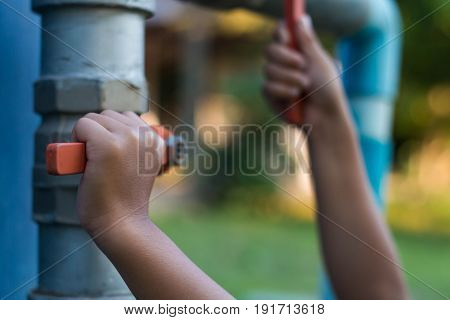 Children try to open the faucet close up.