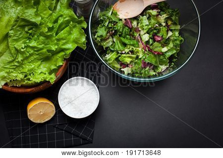 Fresh vegetarian salad mix in a clear glass bowl on a black background. Top view with copy space.