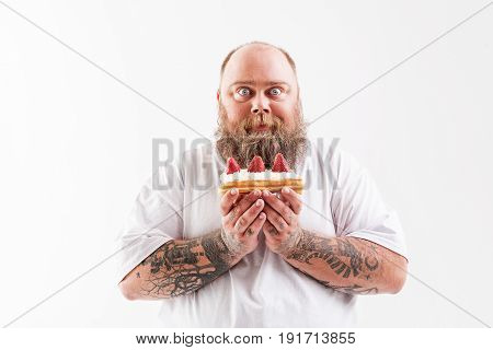 Waist up portrait of happy thick guy eating tasty cake with cream and strawberry. He is standing and staring at camera with desire. Isolated