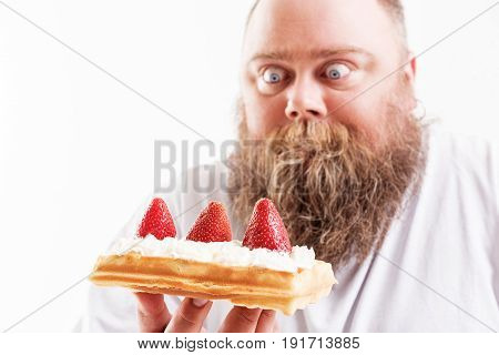 Hungry male fatso is staring at sweet food with desire. Focus on waffle with cream and strawberry in his hand. Isolated