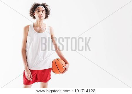 Portrait of confident young skinny man standing and holding ball. Isolated and copy space in right side