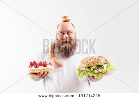 Help yourself with this marvelous lunch. Cheerful thick guy is showing sweet dessert and burger to camera. He is carrying sausages and doughnut. Fatso is looking with excitement and smiling. Isolated