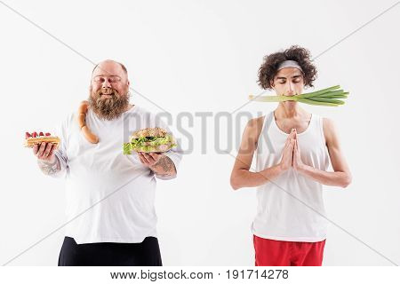 Enjoying own lifestyle. Calm slim boy is meditating with vegetable in his mouth. Joyful fat man is holding unhealthy food and smiling with closed eyes. Isolated