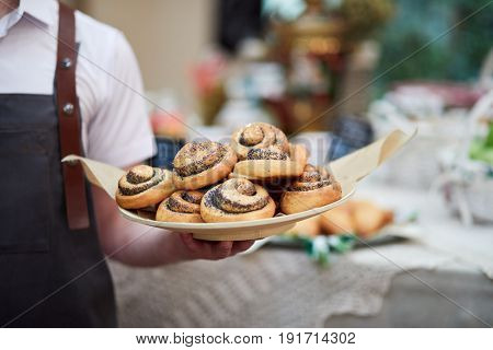 Male waiter stands holding dish with baked rolls with poppy seeds.