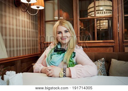 Smiling blond woman sits alone at table in cafe.