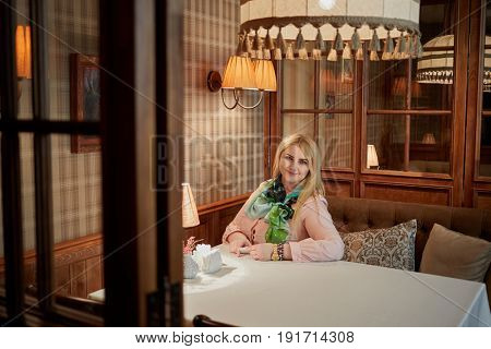 Smiling blond woman sits alone at table in cosy cafe.