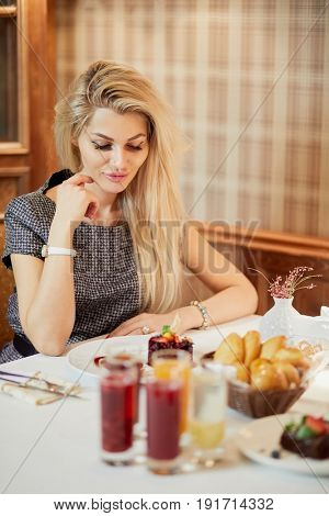 Young blond woman sits at table with fruit drinks and several kinds of desserts.