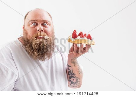 Got caught. Scared fat man is holding sweet unhealthy food with his bead full of cream. He is standing and staring at camera with shock. Isolated and copy space