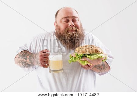 Portrait of glad fat man smelling large sandwich and beer with enjoyment. His eyes are closed with happy smile. Isolated