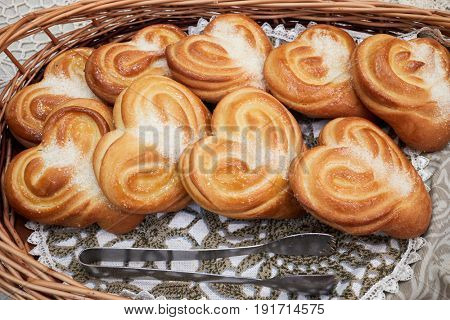 Wicker basket with baked buns with sugar.