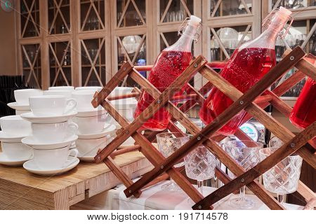 Bottles with red beverage, wine glasses and cups on wooden table.