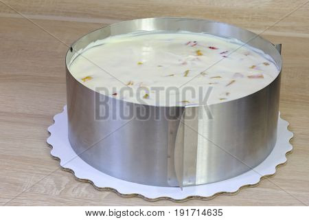 White creamy cake with fruits in metal round shape on table, close-up