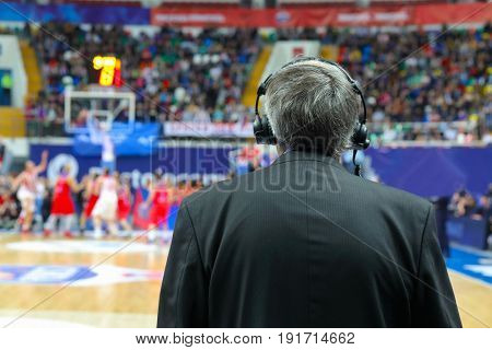 Commentator in headphones and suit at basketball game, back view
