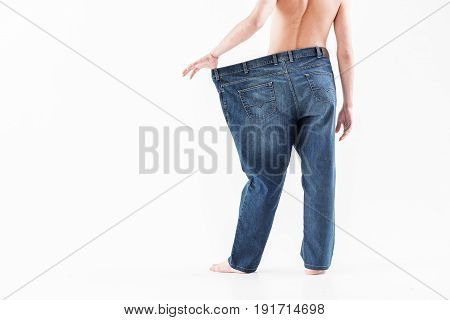 Close up of male legs standing and showing his thin body while stretching oversized pants sideways. Focus on his back. Isolated and copy space