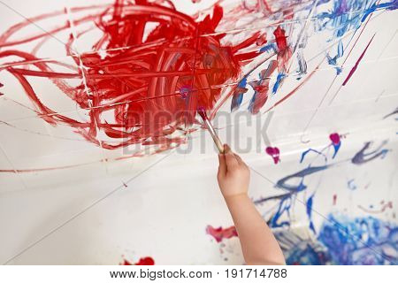 Closeup shot of baby hand arm holding brush painting on wall in bathroom bathtub with red bright paint early education development active childhood concept motion blur effect