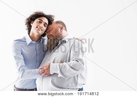 Opposites meet. Happy male gays are hugging and holding hands with love. They are standing and smiling. Isolated and copy space