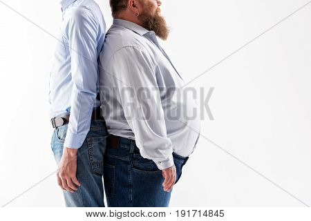 Real opposites. Close up side view of body of two thin and thick men. Fatso is standing with large belly and beard. Isolated and copy space