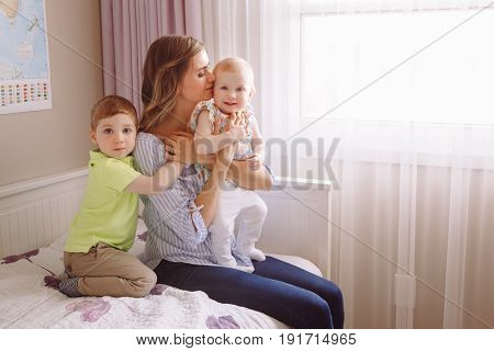 Portrait of beautiful white Caucasian woman mother hugging two cute adorable children kids son and daughter boy and girl sitting on bed near window together family lifestyle concept