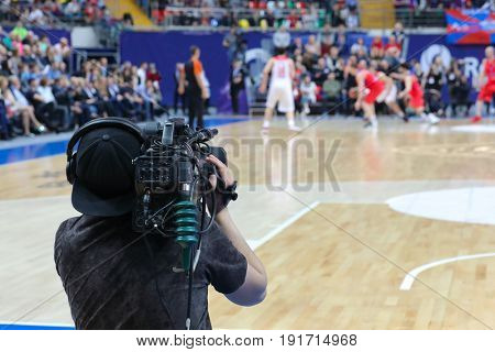 Cameraman works at basketball game in big stadium, back view