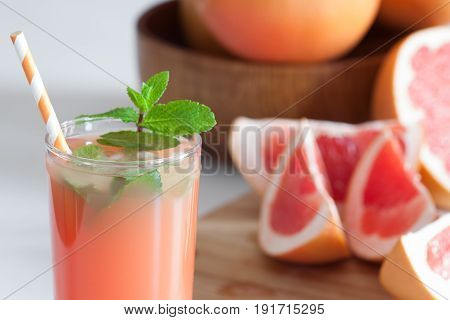Freshly pressed grapefruit juice with mint leaves and ice on white table close up.