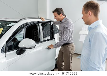 Side view cheerful client looking at car interior while standing near it in dealership. Agent describing information about it