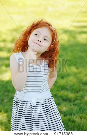 Portrait of cute adorable puzzled little red-haired Caucasian girl child in white striped dress standing in field meadow park outside thinking having fun happy lifestyle childhood concept
