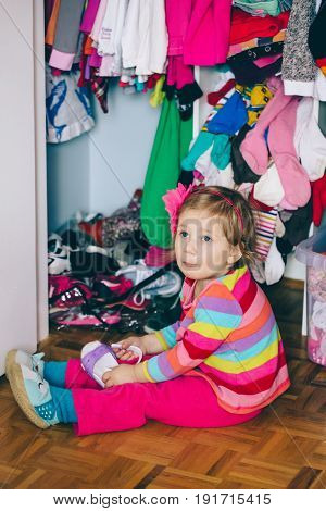 Portrait of cute adorable little white Caucasian girl baby sitting on floor in wardrobe wearing shoes funny emotional face expression lifestyle authentic childhood concept