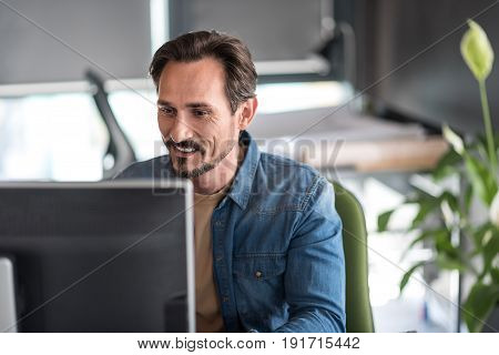 Interested man is sitting near table and using computer for work. He looking at screen with smile. Portrait