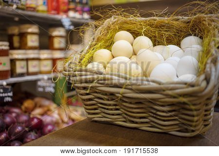 White eggs in basket with straw, shelves with jars out of focus in shop