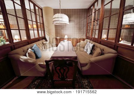 Table with tablecloth in home-style restaurant with couches, lampshades