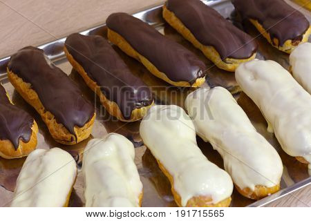 Eclairs with chocolate and white icing on baking sheet, close-up
