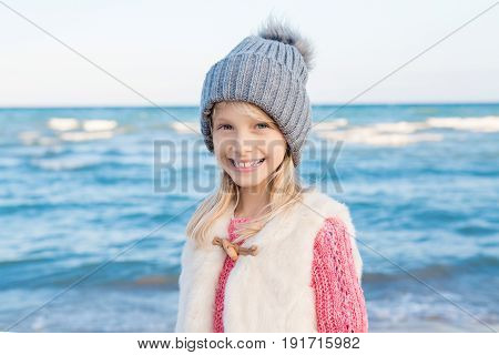 Portrait of smiling blonde white Caucasian child kid girl with long hair wearing white fur jacket gilet and grey hat on sea shore beach looking in camera happy lifestyle childhood