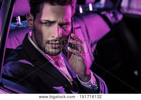 Sexy handsome man having a phone call in the car at the evening