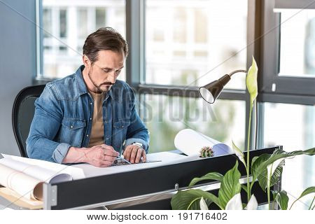 Serious employee is using pencil and scale for work. He create new project. Man sitting at workplace