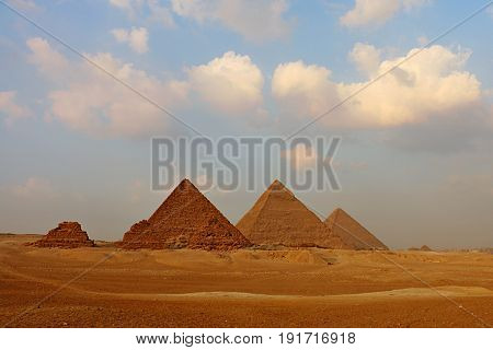 Great Pyramids on the Giza Plateau with Puffy Clouds in a Blue Sky