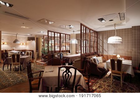 Tables with tablecloths in home-style restaurant with lampshades, carpets