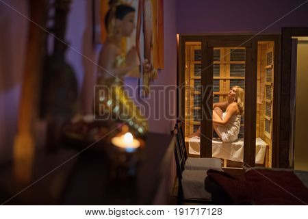 Pretty slim woman in white towel sits in modern sauna in spa with asian decoration