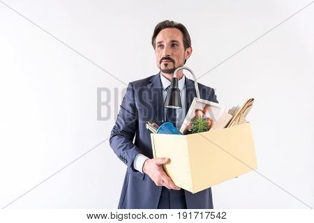 New opportunities. Portrait of positive mature employee is changing his job. He is standing with his belongings and expressing gladness. Isolated background