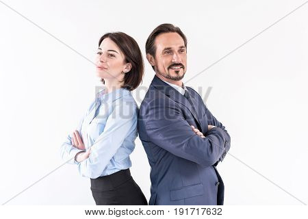 Concept of partnership in business. Portrait of mature bearded man and young woman are standing back to back with crossed arms and looking aside cheerfully. Isolated background