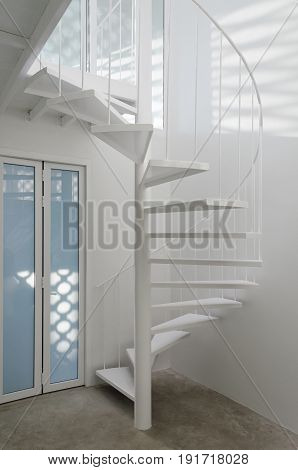 White spiral staircase in modern room with light effect