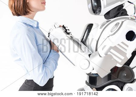 Together forever. Close up arms of young woman and big cyborg. They are looking at each other with passion. Isolated background