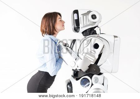 Expectation. Charming elegant young woman is waiting for kiss while standing with robot with closed eyes. Isolated background