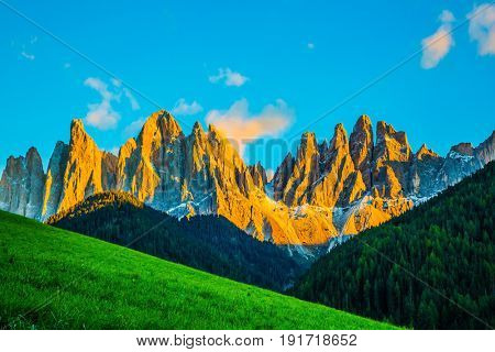 Magnificent serrated cliffs illuminate the summer sunset. The Dolomites. The concept of eco-tourism in Tirol